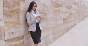 Female worker texting and leaning against wall stock video