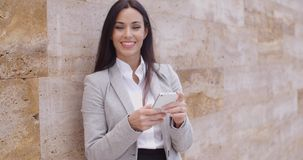 Female worker texting and leaning against wall stock footage