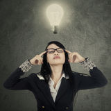 Female worker thinking under bright lamp Stock Photography