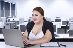 Female worker typing on laptop Stock Photo