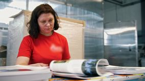 Female worker typography turning pages of a printed magazine. Close up stock footage