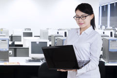 Female worker uses laptop while standing Stock Photos