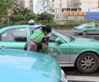 Female worker wash taxi early in the morning Stock Image