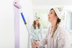 Female worker painting the wall. Female worker wearing paper hat painting the wall with roller royalty free stock photos