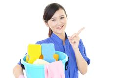 A female Janitorial cleaning service. The female worker who poses happy on white background Royalty Free Stock Photography