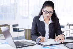 Female worker writes a journal in office Stock Photography