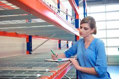 Female worker writing inventory at delivery depot warehouse Royalty Free Stock Photography