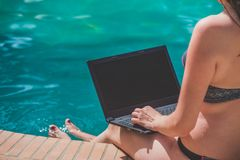 Female working on blank screen laptop at the swimming pool edge Royalty Free Stock Photo