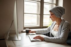 Female working on computer and drinking coffee. At workplace Royalty Free Stock Image