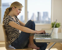 Female working on computer at home Royalty Free Stock Image