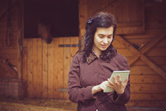 Female working on digital tablet in front of the stable. Woman looking at white digital tablet device in front of the stable with a horse in the background Stock Photo