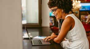 Smiling woman sitting at cafe using laptop royalty free stock photo