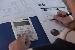 Female working in office, studying using calculator and writing something with documents and chart on table royalty free stock image