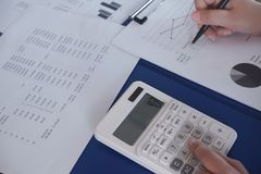 Female working in office, studying using calculator and writing something with documents and chart on table stock image