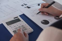 Female working in office, studying using calculator and writing something with documents and chart on table stock photography