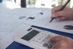 Female working in office, studying using calculator and writing something with documents and chart on table royalty free stock photos