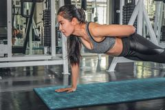 Female working out with push up in gym. Asian female working out with push up in gym stock photo