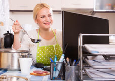Female working on PC. Happy young female in apron working on PC at kitchen Royalty Free Stock Photos
