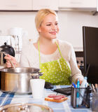 Female working on PC. Positive blonde female in apron working on PC at kitchen Stock Photography