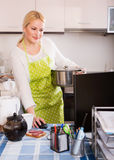 Female working on PC. Smiling young female in apron working on PC at kitchen Stock Photo
