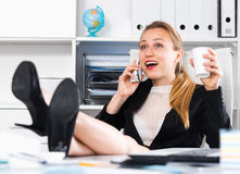Female working and talking on the phone Royalty Free Stock Image