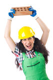 Female workman in green overalls holding brick Stock Photos