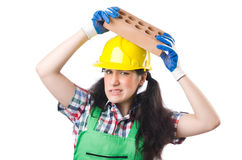 Female workman in green overalls holding brick. The female workman in green overalls holding brick isolated on white Royalty Free Stock Photography