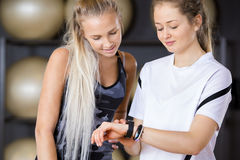Female Workout Friends Using Pedometer In Gym Stock Images