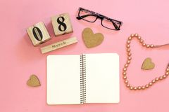 Female workplace with glasses, notebook, wooden calendar, chaplet on pink background. Date of 8 march as a symbol of International. Women`s Day royalty free stock images