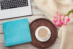 Female workplace with a laptop, cup of coffee, blue notebook, cozy sweater and pink flowers on wooden background.Top view composit. Female workplace with a royalty free stock photo