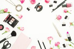 Female workspace with cosmetics, accessories and pink roses on white background. Top view. Flat lay. Beauty blog background. Female workspace with cosmetics Royalty Free Stock Images