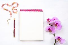 Mockup with notepad, pen and pink orchid, top view Royalty Free Stock Image