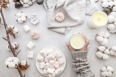 Female workspace in pastel tones. Marshmallows, cotton, candles top view on white marble background. Female workspace with female hands, marshmallows, white royalty free stock images
