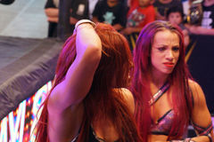 Female wrestler Becky Lynch holds head and Sasha Banks Stock Photos