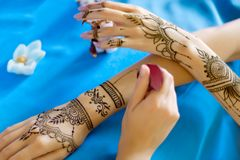 Painted Indian hand with mehndi ornament. Female wrists painted with traditional oriental mehndi ornaments. Process of painting womens hands with henna stock image