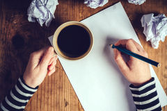 Female writer drinking cup of coffee Stock Images