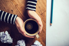 Female writer drinking cup of coffee. Top view of female hands holding cup of coffee above pencils and paper on work desk, retro toned image stock photos