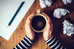 Female writer drinking cup of coffee. Top view of female hands holding cup of coffee above pencils and paper on work desk, retro toned image royalty free stock images