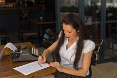 Female writer with vintage typewriter making notes in a coffee s. Female writer with long dark hair, wearing white shirt and red lipstick, making notes in a stock photography