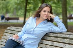 Female writer sitting on park bench. Female writer sitting on the park bench royalty free stock photography