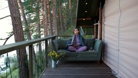 Female Writer Taking Notes Outside Glamping Tent
