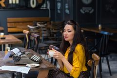 Female writer with vintage typewriter in a coffee shop. Beautiful female writer with long brown hair wearing yellow shirt and polka dot brown skirt, sitting in a stock images