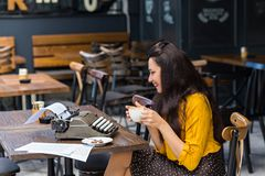 Female writer with vintage typewriter in a coffee shop. Sideview portrait of a beautiful female writer with long brown hair wearing yellow shirt and polka dot stock images