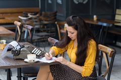 Female writer with vintage typewriter taking notes in a coffee s. Beautiful female writer with long brown hair wearing yellow shirt and polka dot brown skirt stock photo