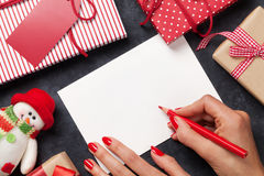 Female writing christmas greeting card and gift wrapping Royalty Free Stock Photography