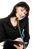 Female writing down notes while talking on phone Royalty Free Stock Images
