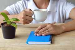 Female writing and drink coffee Royalty Free Stock Images