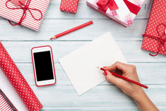 Female writing greeting card and wrapping christmas gifts. Top view with copy space Royalty Free Stock Photography
