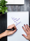 Female writing motivational message in a notebook Royalty Free Stock Photography