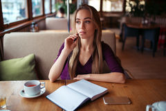 Female writing in notebook in restaurant. Royalty Free Stock Photography